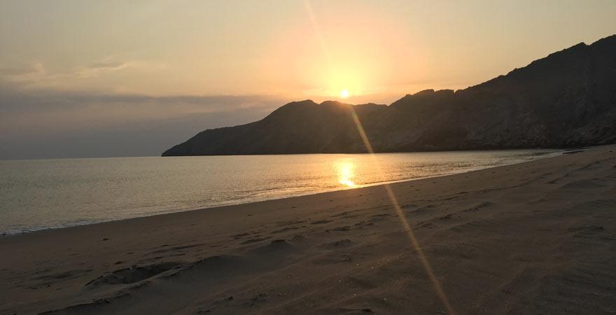 Sonnenuntergang am Stand im Oman