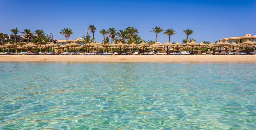 Blick vom Meer auf den Strand von Hurghada mit Stroh-Sonnenschirmen und Palmen