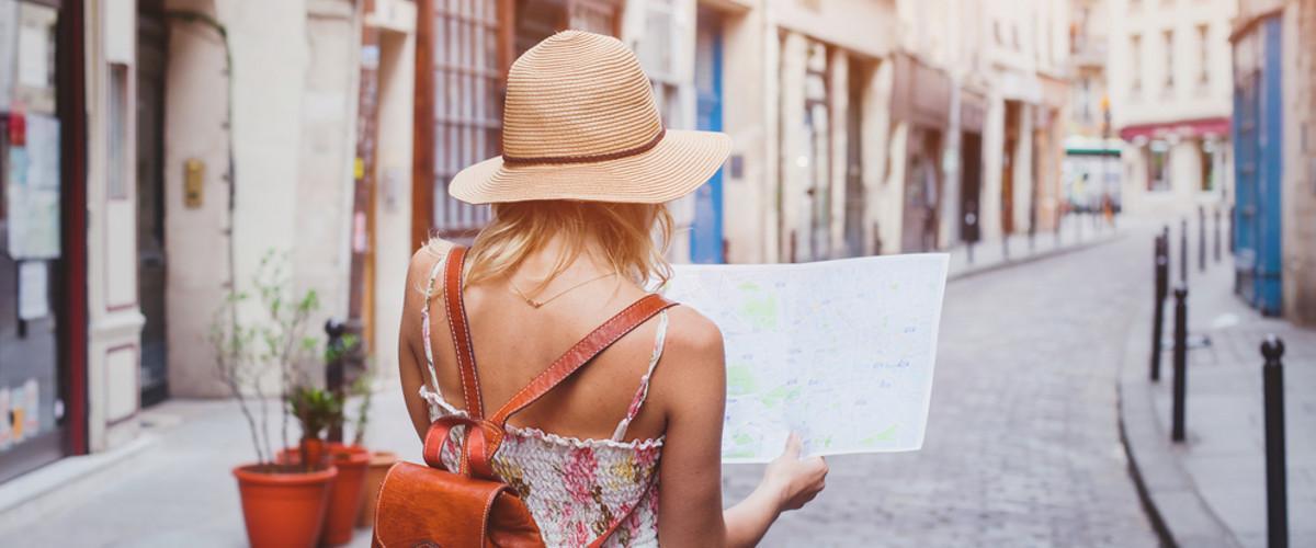 Junges Mädchen bei einem Städtetrip mit Stadtplan.