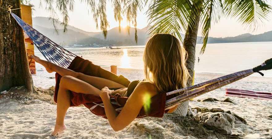Frau in einer Haengematte am Strand