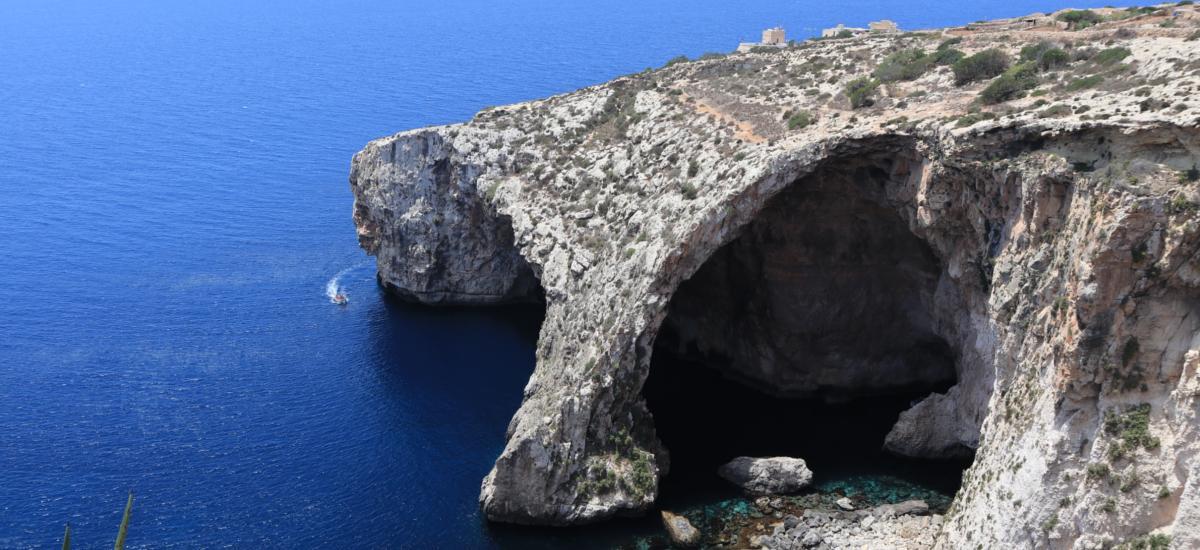 """Blick auf die """"Blue Grotto"""" in Malta - Angebot an verschiedenen Bootstouren zur Grotte - mit glasklarem Wasser"""