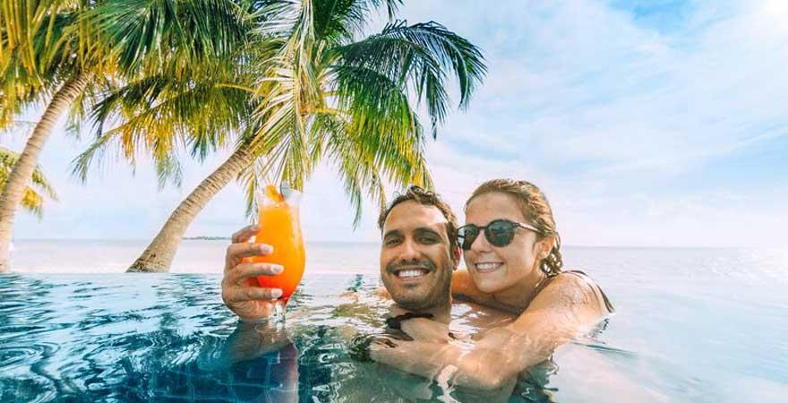Ein par trinkt im Pool einen Cocktail