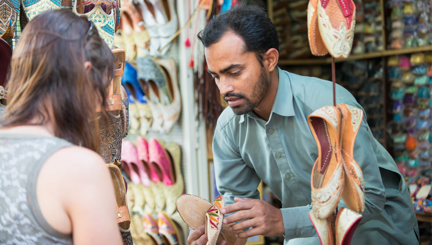 frau kauft auf einem Markt in Dubai schuhe ein