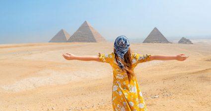 Frau mit Rücken zum Betrachter gewandt in Wüste Ägyptens mit Pyramiden im Hintergrund