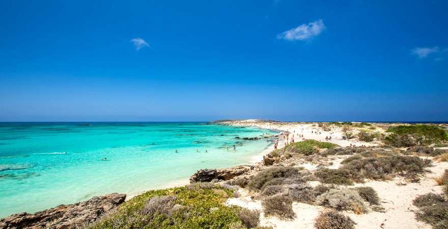 Weißer Strand vor türkisblauem Wasser