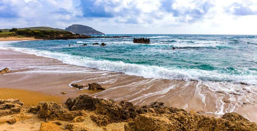 Wellen treffen auf einen Strand mit Felsen und Sand