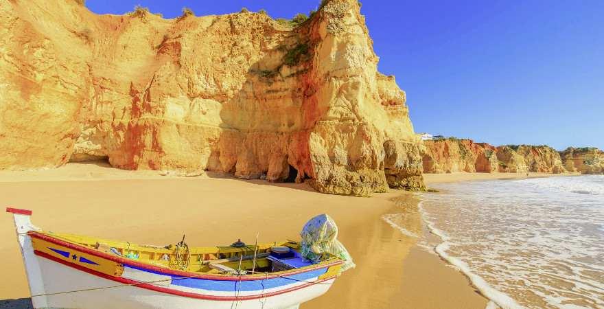 Goldener Sand mit Boot vor Klippen in Portimao