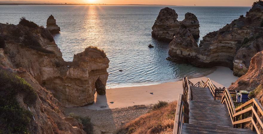 Der Strand Praia do Camilo bei Lago an der Algarve in Portugal bei Sonnenuntergang von der Holztreppe aus umrandet von Felsen, Sand und Meer