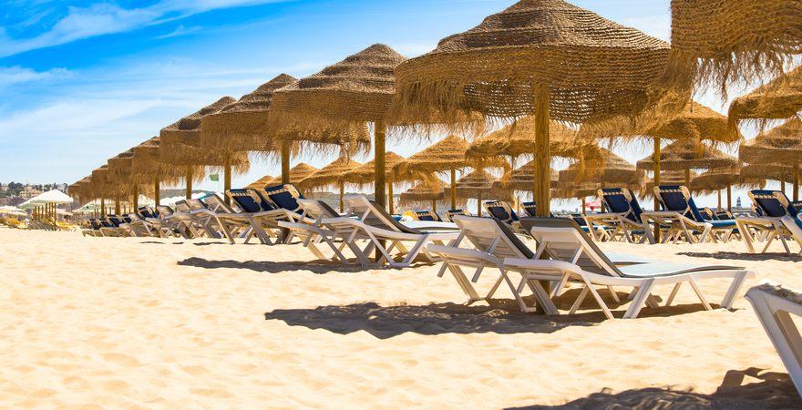 Der Strand Praia das Cabanas in Portugal mit Liegen, Sonnenschirmen und hellem Sand