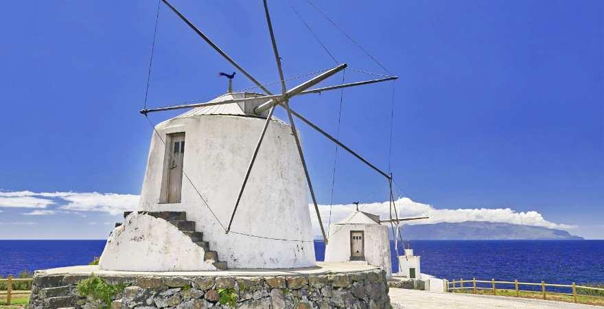 Eine weiße Windmühle vor baluem Himmel auf den Azoren